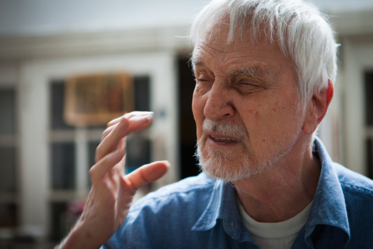Lennart Anderson photographed in his studio up close, gesturing with a dramatic facial expression and hand in the air