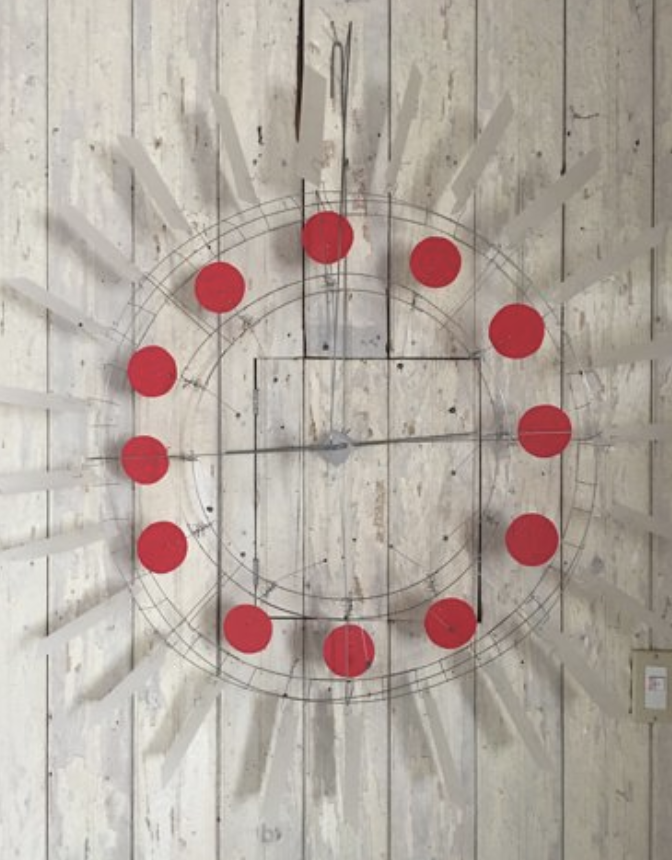 Kinetic sculpture composed of sixteen small red circles arranged in the shape of a circle with Lexan plastic rectangular fins mounted on a pale white paneled wall lit from the left with soft cast shadows