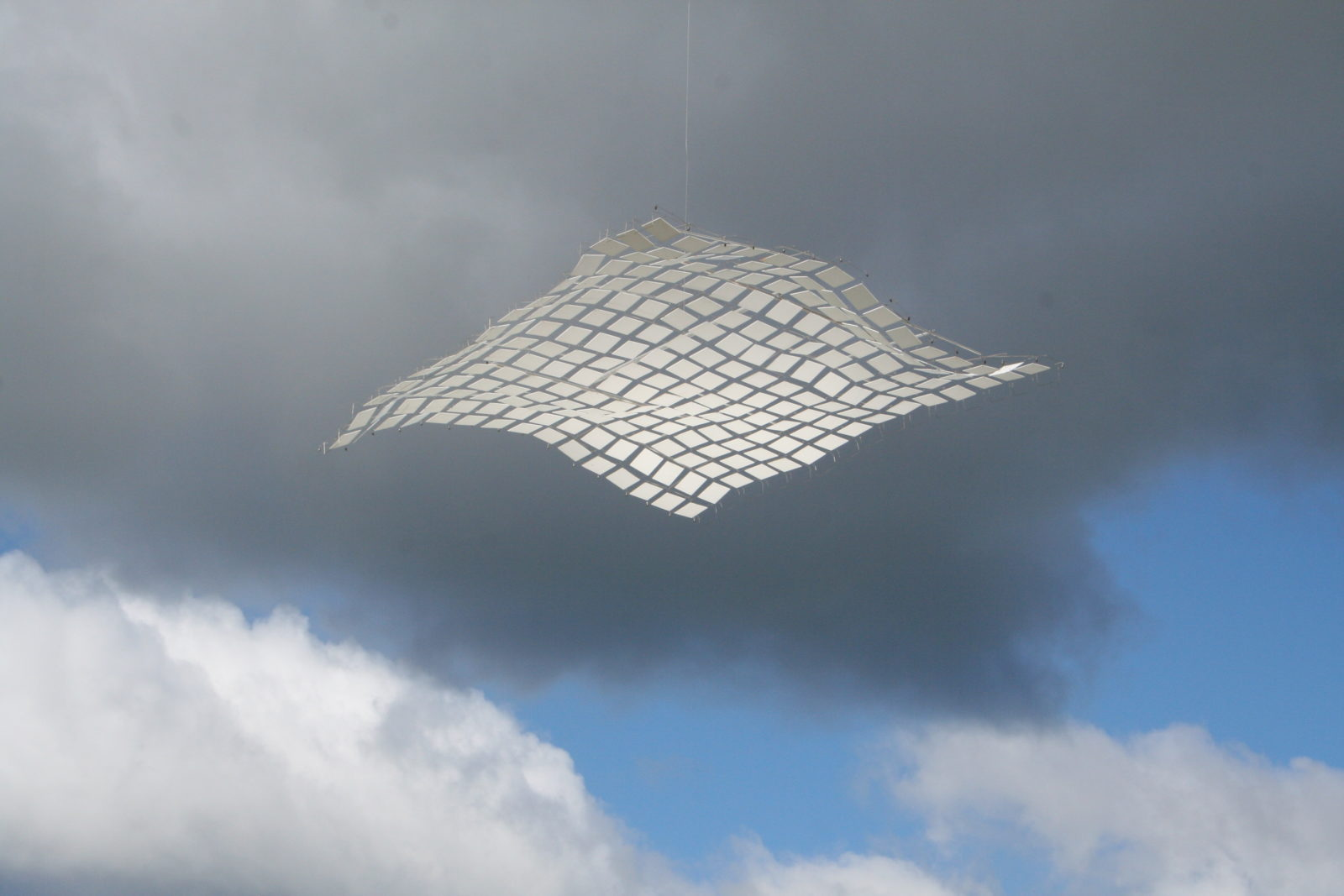 A kinetic sculpture that is like a floating carpet and posed against a stormy sky